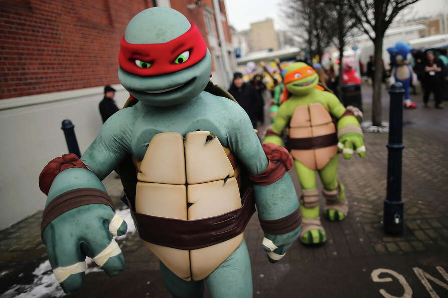 Life size Teenage Mutant Ninja Turtles cartoon characters are led outside for a photocall during the