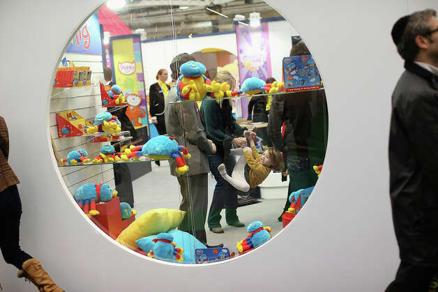 Betsy McCredie, 4, from Glasgow plays inside a trade stand during the 2013 London Toy Fair at Olympia Exhibition Centre on January 22, 2013 in London, England. The annual fair which is organized by the British Toy and Hobby Association, brings together toy manufacturers and retailers from around the world. Photo: Dan Kitwood, Getty Images / 2013 Getty Images