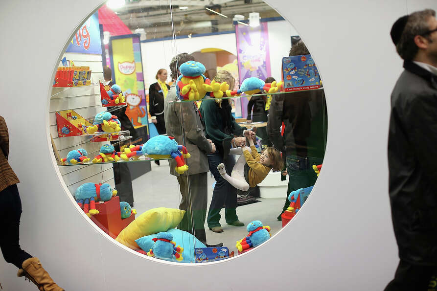 Betsy McCredie, 4, from Glasgow plays inside a trade stand during the 2013 London Toy Fair at Olympi