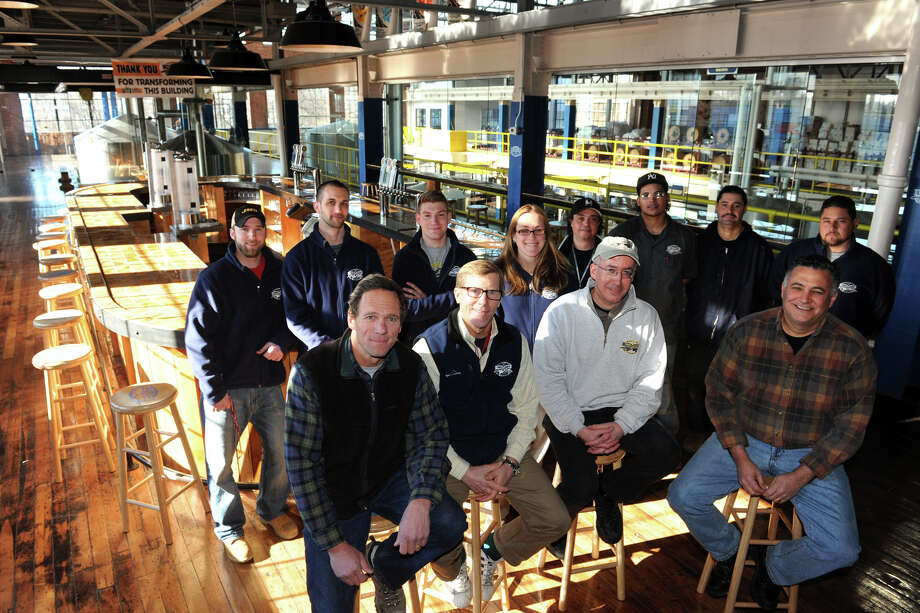 At Two Road Brewing Company, in Stratford, owners and partners, seated left to right, Peter Doering, Brad Hittle, Phil Markowki and Clem Pellani pose in the brewery's tasting room with the brewery staff, Jan. 2nnd, 2013. Photo: Ned Gerard / Connecticut Post