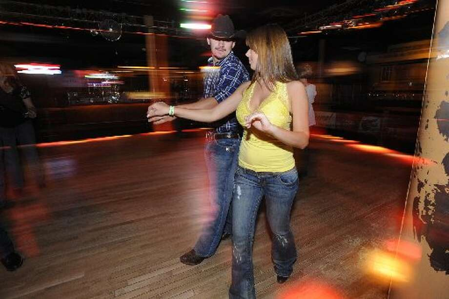 At Whiskey River, Beaumont couple, Cody Harrington and his fiancé Katy Stanford take advantage of free dance lessons, practicing the Texas Two-Step on Wednesday night. Wednesday, July 22, 2009. Valentino Mauricio/cat5
