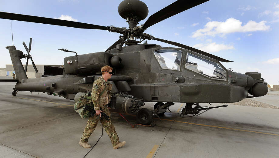 Prince Harry walks past an Apache helicopter at the British controlled flight-line in Camp Bastion in October 31, 2012 in Afghanistan. Prince Harry has served as an Apache Helicopter Pilot/Gunner with 662 Sqd Army Air Corps, from September 2012 for four months until January 2013. Photo: WPA Pool, Getty Images / 2012 Getty Images