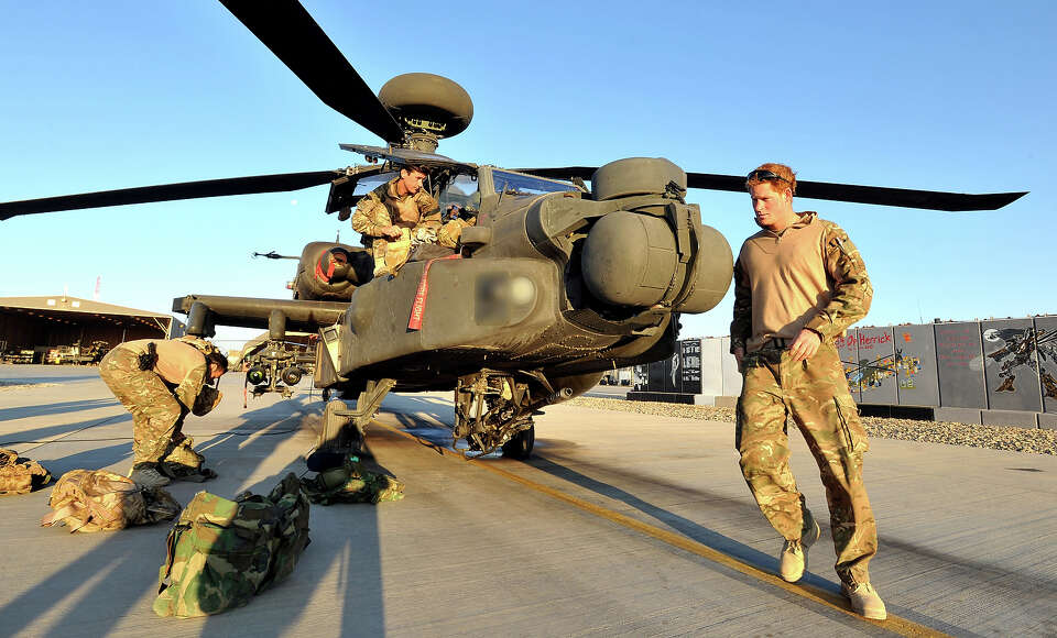 Prince Harry (R)  does a pre-flight check of his Apache Helicopter after starting his 12 hour VHR (v