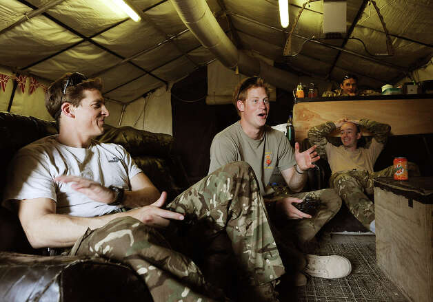 Prince Harry (C)  celebrates as he scores a goal during a computer football game with his fellow Apache Helicopter Pilot Capt Simon Beattie (L), during their 12 hour VHR (very high ready-ness) shift at the British controlled flight-line in Camp Bastion on November 3, 2012 in Afghanistan. Prince Harry has served as an Apache Helicopter Pilot/Gunner with 662 Sqd Army Air Corps, from September 2012 for four months until January 2013. Photo: WPA Pool, Getty Images / 2013 Getty Images