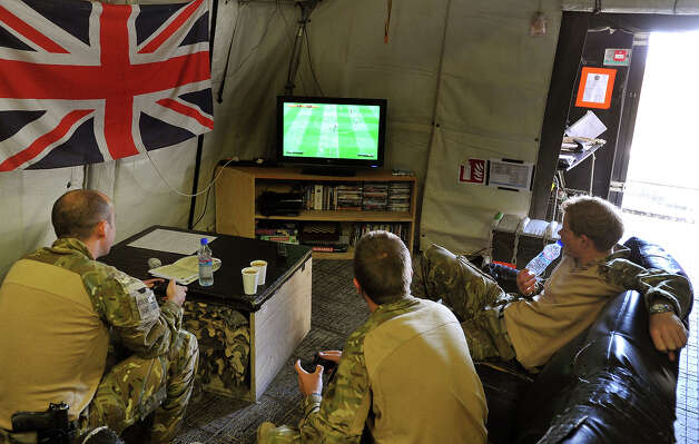 Prince Harry (R) relaxes during a computer football game with fellow Apache Helicopter crew members, during their 12 hour VHR (very high ready-ness) shift at the British controlled flight-line in Camp Bastion on November 1, 2012 in Afghanistan, where he has served as an Apache Helicopter Pilot/Gunner with 662 Sqd Army Air Corps, from September 2012 for four months until January 2013. Photo: WPA Pool, Getty Images / 2013 Getty Images