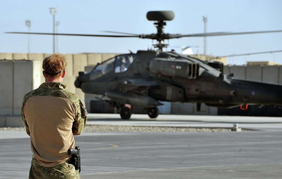 Prince Harry watches the return from a mission of an Apache helicopter at the British controlled fli