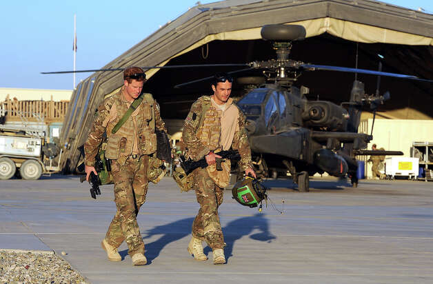 Prince Harry (L) walks to his Helicopter with a fellow pilot at the British controlled flight-line in Camp Bastion on November 1, 2012 in Afghanistan. Prince Harry has served as an Apache Helicopter Pilot/Gunner with 662 Sqd Army Air Corps, from September 2012 for four months until January 2013. Photo: WPA Pool, Getty Images / 2012 Getty Images