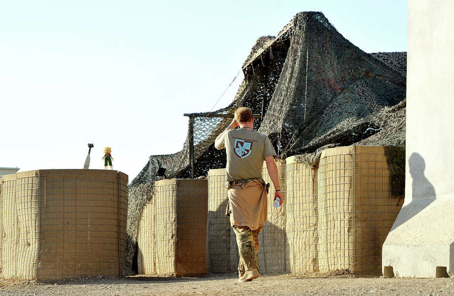 Prince Harry (L) walks towards the VHR (very high ready-ness) tent to start his 12 hour shift at the British controlled flight-line in Camp Bastion on November 3, 2012 in Afghanistan. Prince Harry has served as an Apache Helicopter Pilot/Gunner with 662 Sqd Army Air Corps, from September 2012 for four months until January 2013. Photo: WPA Pool, Getty Images / 2012 Getty Images