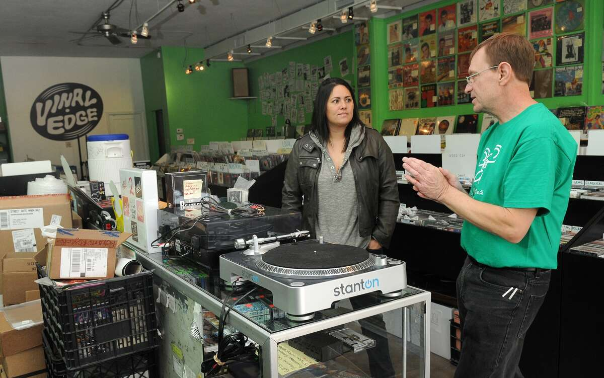 Veronica Caycedo discusses turntables with Chuck Roast, owner of Vinal Records in the Heights.