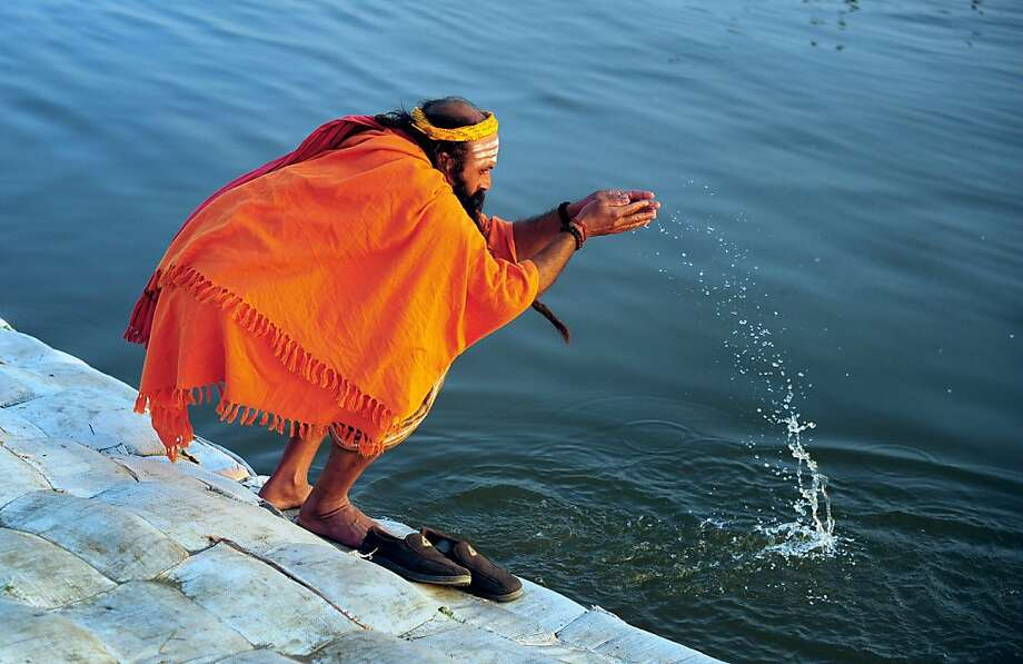 Ablution amid the pollution: An Indian sadhu performs evening prayers on the bank of the Sangam, the confluence of the contaminated rivers Ganges and Yamuna (and the mythical Saraswati) during the Maha Kumbh Mela in Allahabad. Photo: Sanjay Kanojia, AFP/Getty Images
