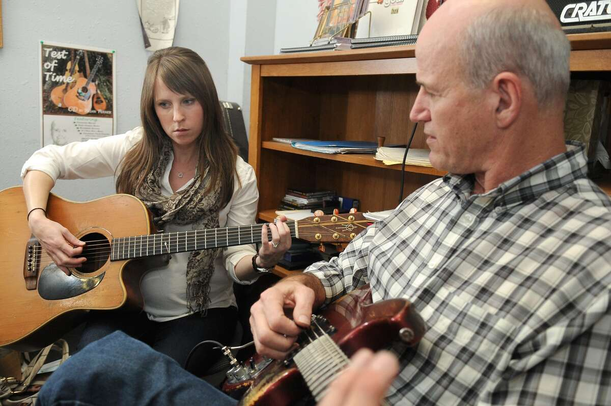 Elizabeth Trask, 29, from left, of Humble, plays an acoustic guitar during her lesson with guitar instructor Brian Turner, of Porter, at the Humble Music Center. Freelance photo by Jerry Baker