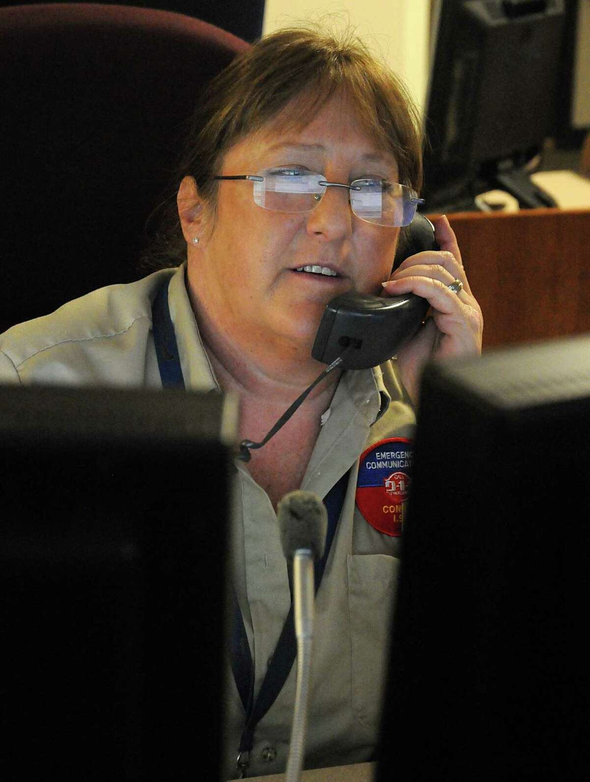 Conroe ISD police department telecommunications operator Lisa Dunham keeps the lines of communication open while tracking the computers and banks of cameras designed to keep track of all schools and other facilities in the district.