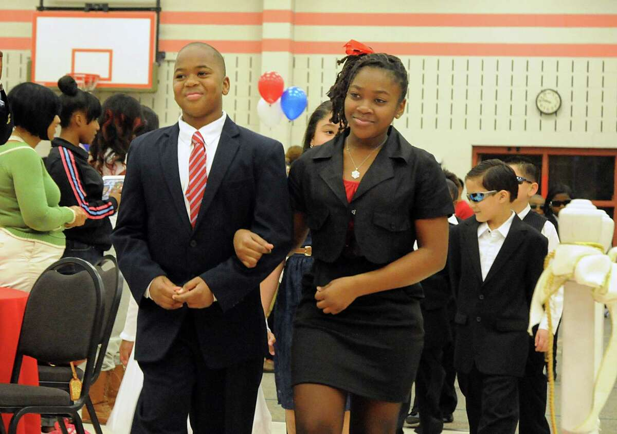 President Barack Obama, Jaylen Odom, and First Lady Michelle Obama, Ayana Elliott, walk the red carpet during Spring ISD's Heritage Elementary School mock inaugural ball.