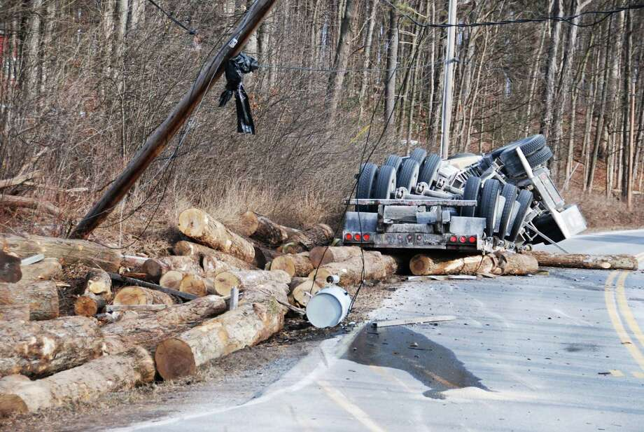 A portion of Route 32 in Bethlehem was closed Tuesday after a logging truck lost its cargo and toppled over - taking out a power line and transformer. (Tom Heffernan / Times Union)
