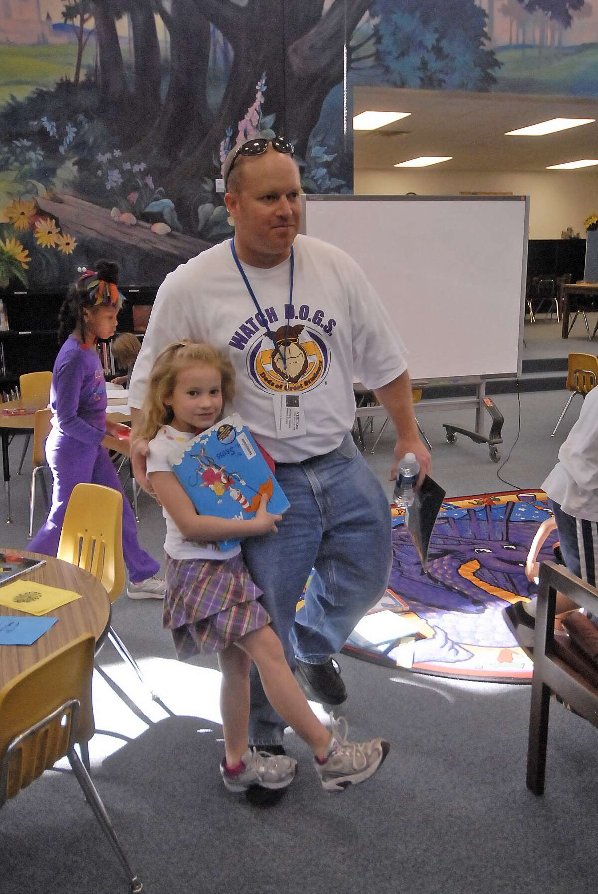 Nottingham Country Elementary Watch D.O.G.S. member Jeff Tootle helps his seven-year-old daughter Katie Tootle during a trip to the library.