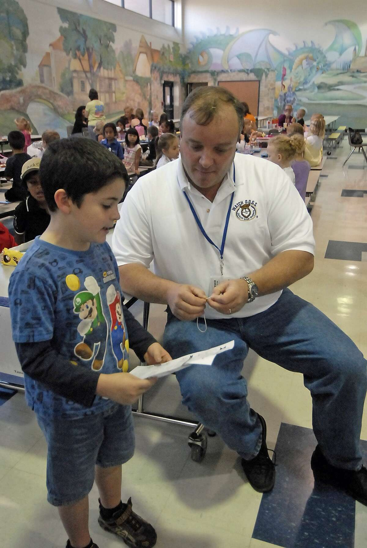 Nottingham Country Elementary Watch D.O.G.S. member Curt Bigge helps his seven-year-old son Tom Bigge with a project.