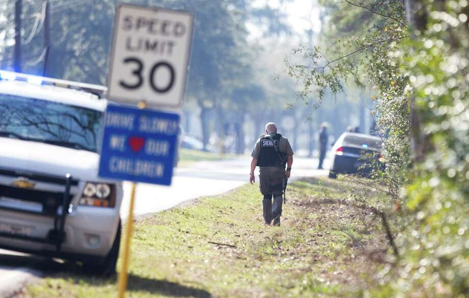 A sheriff's deputy walks along the road toward the Lone Star College campus following a shooting at the north Harris County school Tuesday, Jan. 22, 2013, in Houston. Photo: Brett Coomer, Houston Chronicle / © 2013 Houston Chronicle
