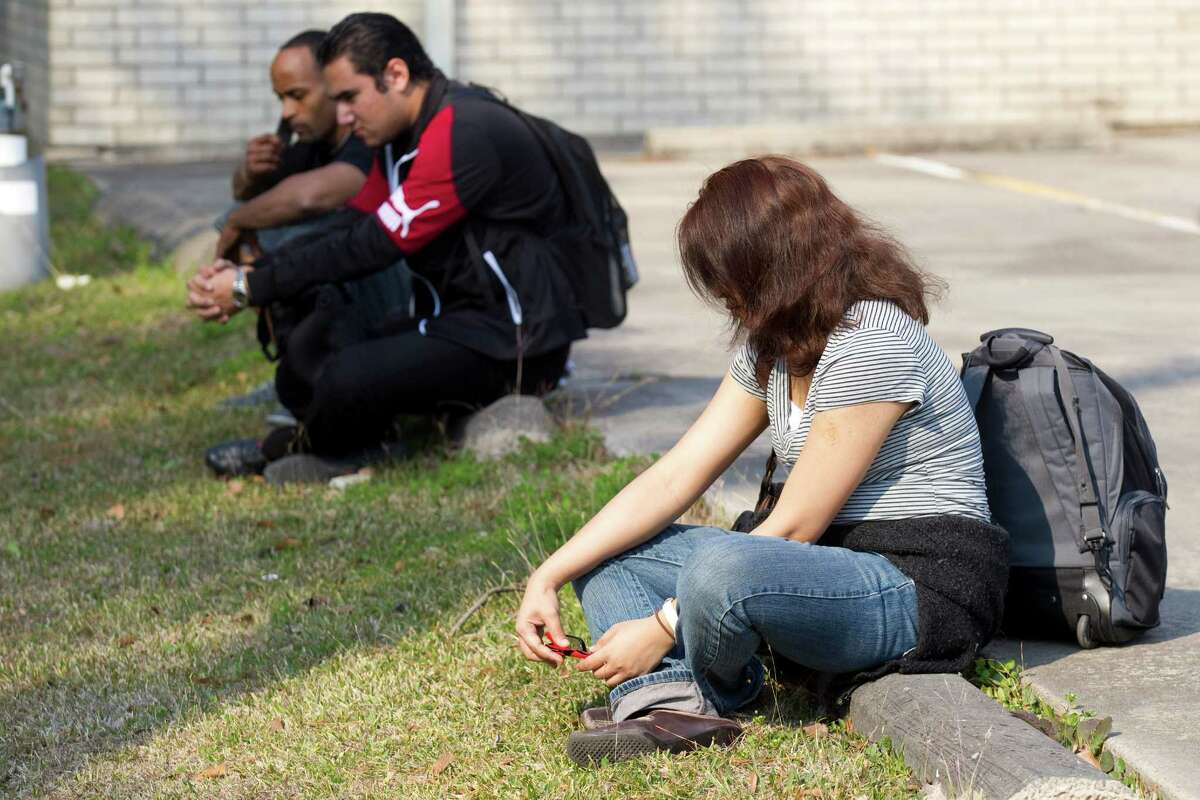 Lone Star College students sit near a parking lot after they were evacuated from the campus following a shooting at the north Harris County school Tuesday, Jan. 22, 2013, in Houston.