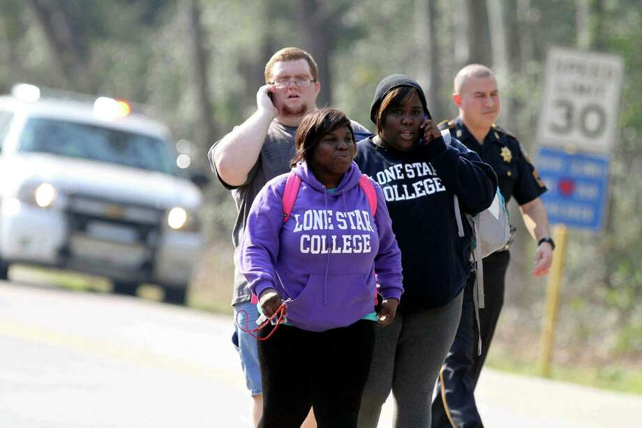 Women wearing Lone Star College sweatshirts and a man walk near Lone Star College in Houston, which was placed on lockdown Tuesday, Jan. 22, 2013, after a shooting that wounded three people and sent students fleeing for safety. (AP Photo/The Courier of Montgomery County, Jason Fochtman) Photo: Jason Fochtman, Associated Press / The Courier of Montgomery County