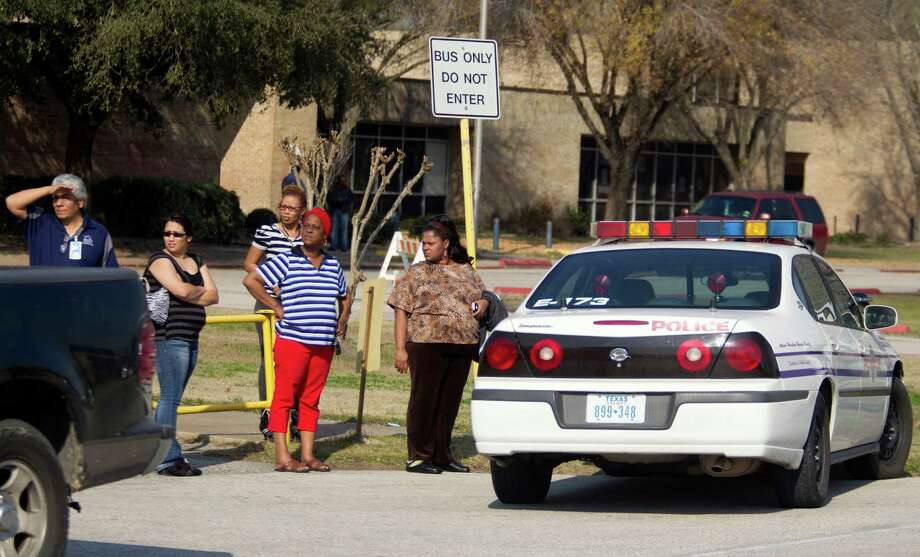 Parents wait to pick up their children outside Nimitz High School after it was placed on lockdown after a shooting happened nearby on Lone Star College North Harris campus on Tuesday, Jan. 22, 2013 in Houston. The shooting wounded three people and sent students fleeing for safety as officials placed the college campus on lockdown, officials said. Harris County Sheriff's Maj. Armando Tello said authorities had detained a person of interest. Police did not provide any details about the people who were wounded.  (AP Photo/Patric Schneider) Photo: Patric Schneider, Associated Press / FR170473 AP