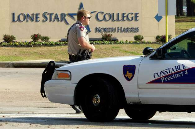 A Harris Precinct 4 Constable blocks off an entrance to the Lone Star College North Harris campus after a shooting on Tuesday, Jan. 22, 2013 in Houston. The shooting on campus wounded three people and sent students fleeing for safety as officials placed the campus on lockdown, officials said. Harris County Sheriff's Maj. Armando Tello said authorities had detained a person of interest. Police did not provide any details about the people who were wounded.  (AP Photo/Patric Schneider) Photo: Patric Schneider, Associated Press / FR170473 AP