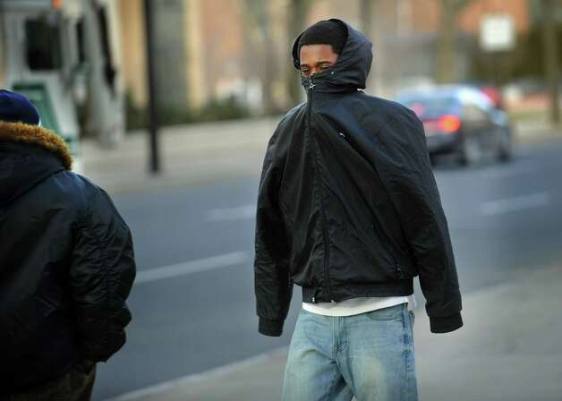 A man keeps his arms inside his jacket to stay warm in a frigid wind on State Street in downtown Bridgeport on Tuesday, January 22, 2013. Photo: Brian A. Pounds