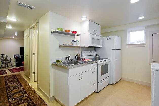 Lower-level guest quarters kitchen of 406 21st Ave. The 2,340-square-foot house, built in 1900, has four bedrooms and 3.25 bathrooms exposed-wood railings, French doors and front and back decks on a 1,495-square-foot lot. It's listed for $519,950. Photo: Courtesy Dorothy Driver/Windermere Real Estate