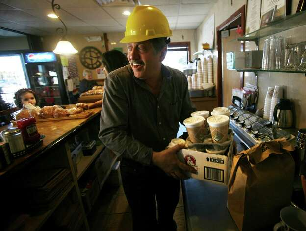 Pop's Family Restaurant owner Gus Grigoriadis brings coffee and breakfast sandwiches to construction workers building his new restaurant on Old Gate Lane in Milford. Grigoriadis has been leasing the current New Haven Avenue location for 22 years. Photo: Brian A. Pounds / Connecticut Post