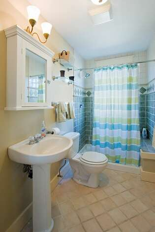 Bathroom of 406 21st Ave. The 2,340-square-foot house, built in 1900, has four bedrooms and 3.25 bathrooms -- including a separate, lower-level guest quarters -- exposed-wood railings, French doors and front and back decks on a 1,495-square-foot lot. It's listed for $519,950. Photo: Courtesy Dorothy Driver/Windermere Real Estate