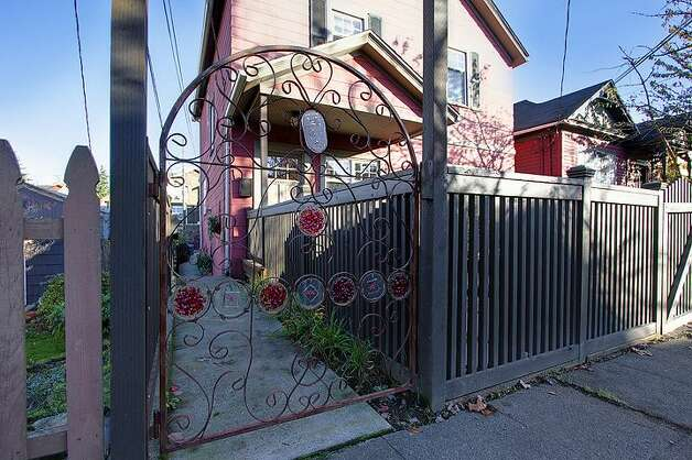 Garden gate of 406 21st Ave. The 2,340-square-foot house, built in 1900, has four bedrooms and 3.25 bathrooms -- including a separate, lower-level guest quarters -- exposed-wood railings, French doors and front and back decks on a 1,495-square-foot lot. It's listed for $519,950. Photo: Courtesy Dorothy Driver/Windermere Real Estate