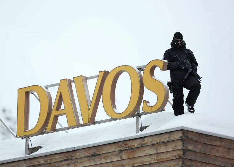 An armed police officer stands on the snow-covered rooftop of the Hotel Davos and looks out over the