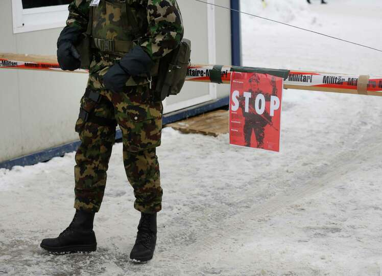A member of the Swiss army stands guard at a security barrier near the Congress Center, the venue fo