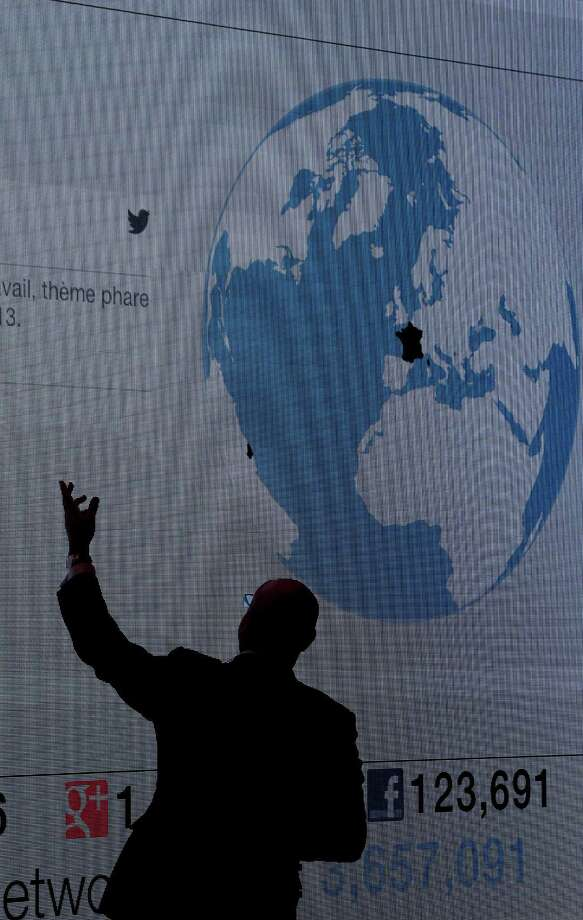 A man is seen silhouetted against a video screen inside one of the forum halls at the Congress Center, the venue for the WEF meeting in Davos, Switzerland, on Tuesday, Jan. 22, 2013. World leaders, Influential executives, bankers and policy makers arrive in the Swiss Alps for the 43rd annual meeting of the World Economic Forum in Davos, the five day event runs from Jan. 23-27. Photographer: Jason Alden/Bloomberg Photo: Jason Alden, Bloomberg / Copyright 2013 Bloomberg Finance LP, All Rights Reserved.