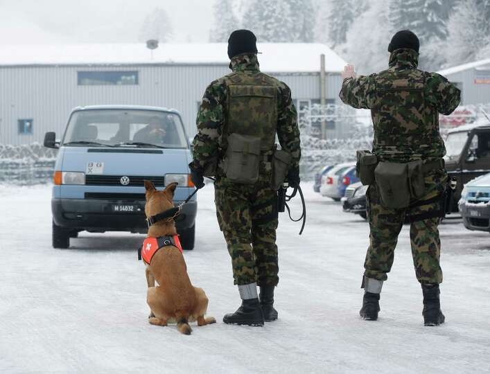 Dog handlers from the Swiss army practice an arrest during a security exercise at their base in Thus