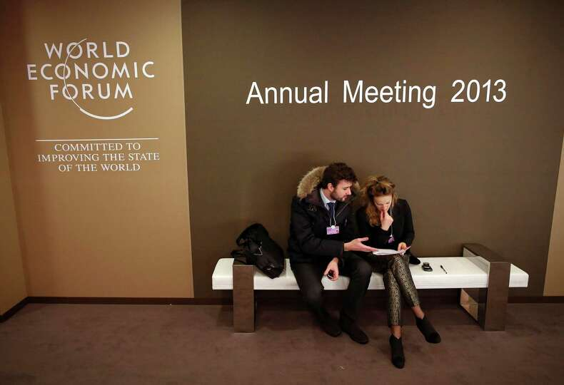 Attendees of the World Economic Forum (WEF) check paperwork as they sit in the Congress Center, the