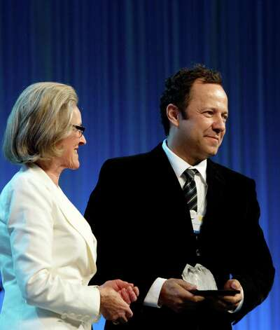 Brazilian artist Vik Muniz (R) receives a Crystal award from Hilde Schwab, Chairperson and Co-Founder of the Schwab Foundation for Social Entrepreneurship, during the Crystal Award Ceremony of the World Economic Forum (WEF) on January 22, 2013 at the Swiss resort of Davos. The WEF will take place from January 23 to 27. AFP PHOTO / JOHANNES EISELEJOHANNES EISELE/AFP/Getty Images Photo: JOHANNES EISELE, AFP/Getty Images / AFP