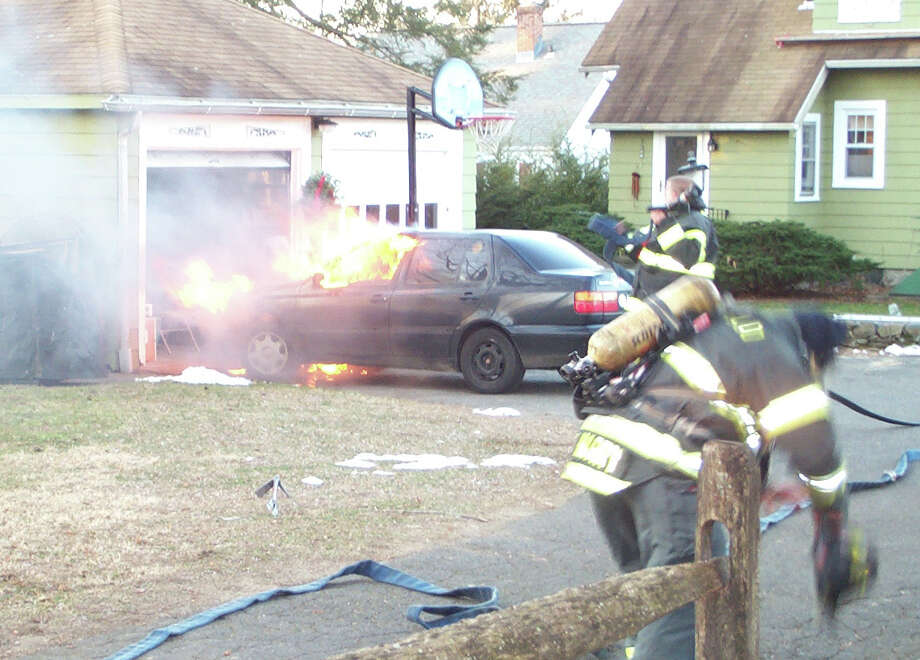 Flames billow from a car that caught fire Tuesday on Church Hill Road as firefighters arrive on the scene. FAIRFIELD CITIZEN, CT 1/22/13 Photo: Fairfield Fire Department / KODAK DC5000 ZOOM DIGITAL CAMERA