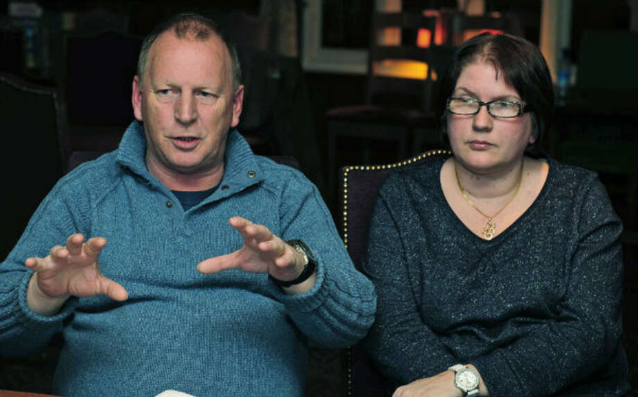 Former hostage at the Algerian natural gas Plant, Peter Hunter, 53, in Durham, England, recounts his ordeal after he was reunited with his wife Kerry, right, Monday Jan. 21, 2013. He spent days in hiding at a secret location during the terror siege at the In Amenas natural gas plant desert complex in Algeria. Hunter said he never saw any terrorists during the crisis, but he followed company procedure and hid in a secret location.