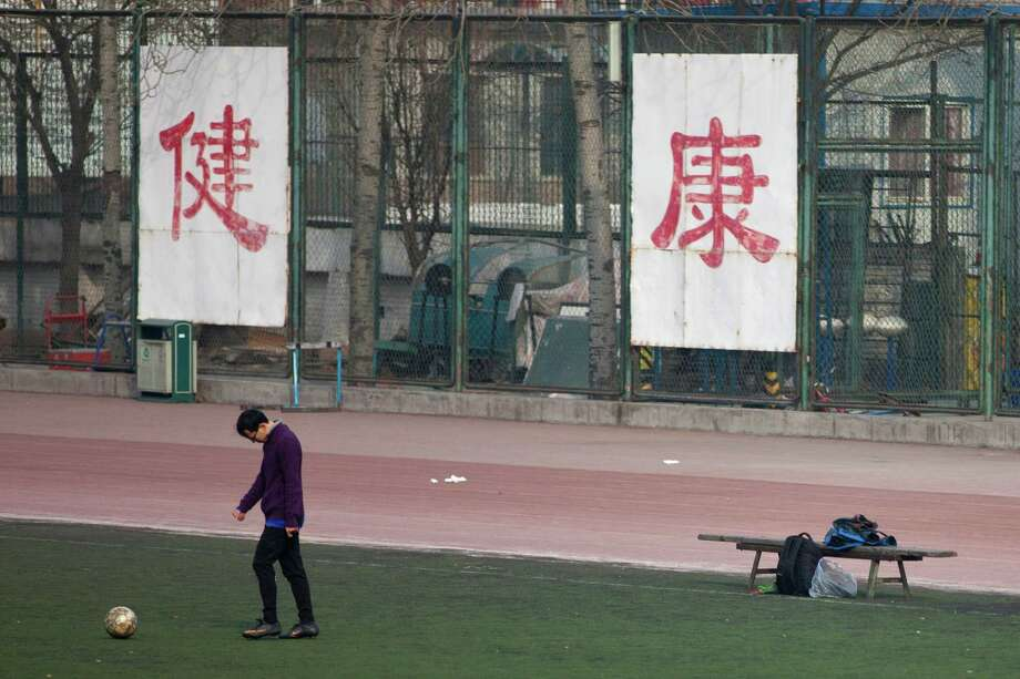 """A college student kicks a soccer ball last week in front of Chinese characters reading """"good health"""" at a park in Beijing. Despite success in recent Olympic Games, China has found itself in a crisis of declining fitness. Photo: Alexander F. Yuan, STF / AP"""