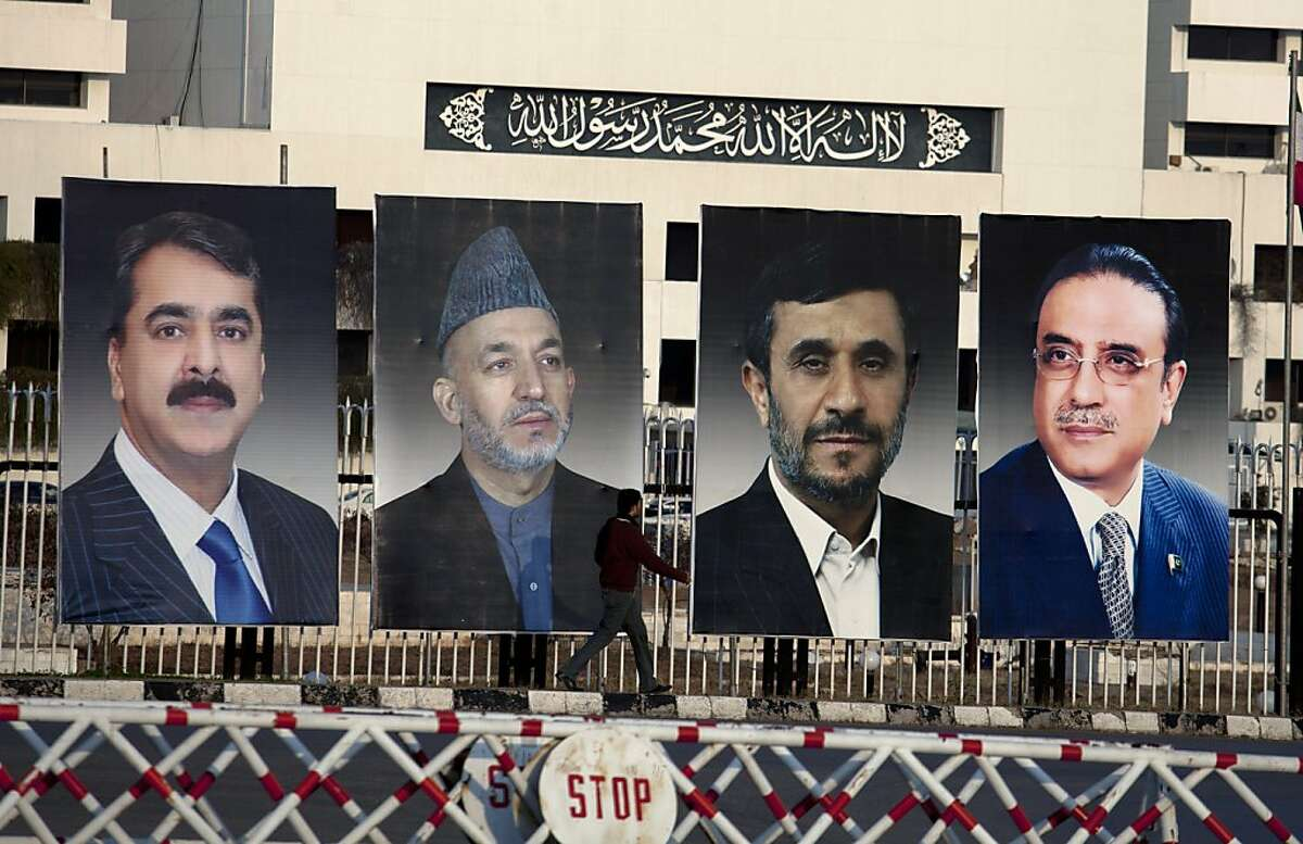 A man walks past pictures of, from left, Pakistan's Prime Minister Yousaf Raza Gilani, Afghan President Hamid Karzai, Iranian President Mahmoud Ahmedinejad and Pakistan's President Asif Ali Zardari, displayed outside the Parliament in Islamabad, Pakistan on Thursday, Feb 16, 2012. The Presidents of Afghanistan and Iran convened in Pakistan for a three-way summit that is expected to focus on specific steps Islamabad can take to facilitate peace talks with the Afghan Taliban. The translation of Arabic inscription is