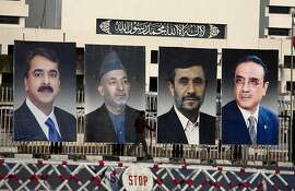 "A man walks past pictures of, from left, Pakistan's Prime Minister Yousaf Raza Gilani, Afghan President Hamid Karzai, Iranian President Mahmoud Ahmedinejad and Pakistan's President Asif Ali Zardari, displayed outside the Parliament in Islamabad, Pakistan on Thursday, Feb 16, 2012. The Presidents of Afghanistan and Iran convened in Pakistan for a three-way summit that is expected to focus on specific steps Islamabad can take to facilitate peace talks with the Afghan Taliban. The translation of Arabic inscription is ""There is no God only Allah, Mohammed is the messenger of Allah."" (AP Photo/B.K. Bangash)"
