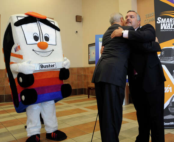 "Henry R. Muñoz III, chairman of the VIA Board of Trustees, right, embraces Bexar County Commissioner Tommy Adkisson as ""Buster,"" the ViA Metropolitan Transit mascot, watches during a SmartWaySA press conference on Aug. 26, 2009. SmartWay SA is an outreach program to garner public input about proposed public transportation expansion. Photo: BILLY CALZADA, SAN ANTONIO EXPRESS-NEWS / gcalzada@express-news.net"