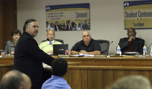Henry Muñoz III (standing, left) makes a presentation to the San Antonio Independent School District Board on Dec. 29, 2010. Muñoz, representing Muñoz Jacobs, was there with two other groups that were vying for the position of Program Administrator for SAISD's 2010 Bond Program. Photo: JOHN DAVENPORT, SAN ANTONIO EXPRESS-NEWS / jdavenport@express-news.net