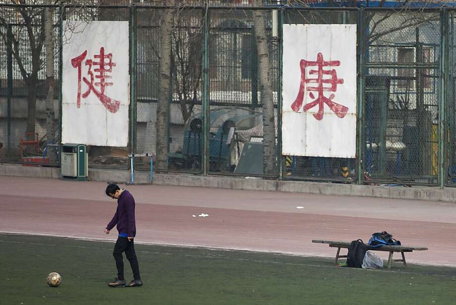 "A college student in Beijing kicks a soccer ball in front of banners reading ""good health."" Schools have been urged to beef up their physical education. Photo: Alexander F. Yuan, Associated Press"