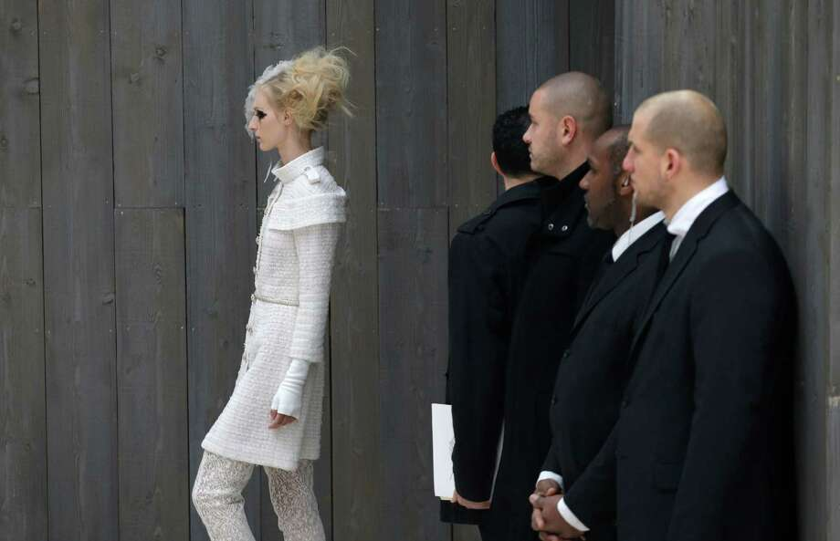 Security officers watch a model wearing a creation by German fashion designer Karl Lagerfeld for Chanel. Photo: AP