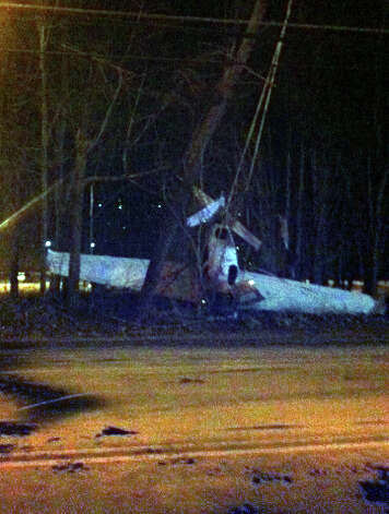 A plane crashed in the South St. area of Danbury, Conn. Tuesday evening, Jan. 22, 2013.  The plane used a parachute to break its fall and three passengers escaped major injury. Photo: John Pirro / The News-Times