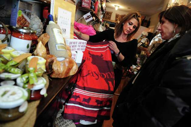 Owner Mersene Norbom, left, talks with customer Wendy Cruikshank, of Darien, Tuesday, Jan. 22, 2013 at her gift shop, Indulge by Mersene, in Westport, Conn. Photo: Autumn Driscoll / Connecticut Post