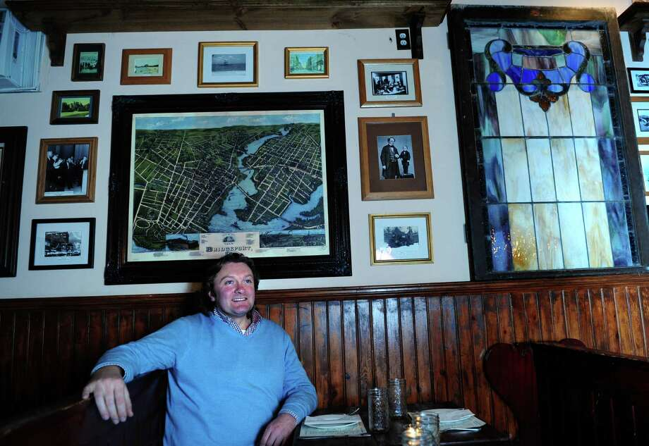 Chris Andrews, part-owner of Tautog Tavern, a New England-style pub in the Black Rock section of Bridgeport, Conn. sits at one of the booths under some of the iconic scenes of Bridgeport that line the pub's walls. Photo: Autumn Driscoll / Connecticut Post