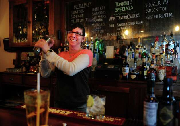 Emilie Robinson, part-owner and bar manager, mixes up a margarita at Tautog Tavern, a New England-style pub in the Black Rock section of Bridgeport, Conn. Photo: Autumn Driscoll / Connecticut Post