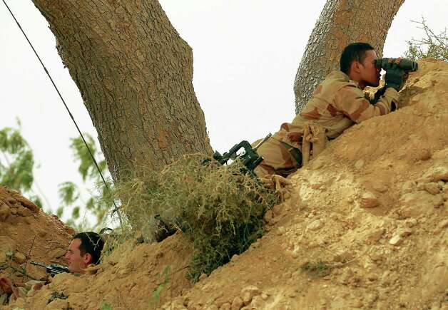 French foreign legionnaires take position outside  Marakala, central Mali, some 240kms (140 miles) from Bamako Tuesday, Jan. 22, 2013.  French troops in armored personnel carriers rolled through the streets of Diabaly on Monday, winning praise from residents of this besieged town after Malian forces retook control of it with French help a week after radical Islamists invaded. The Islamists also have deserted the town of Douentza, which they had held since September, according to a local official who said French and Malian forces arrived there on Monday as well. (AP Photo/Jerome Delay) Photo: Jerome Delay